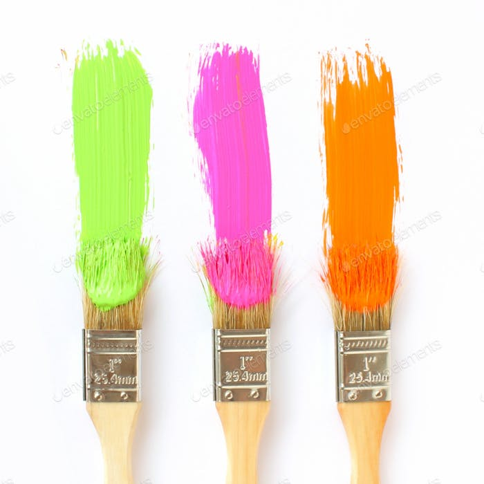 Drei Pinsel machen bunte Farbstreifen.