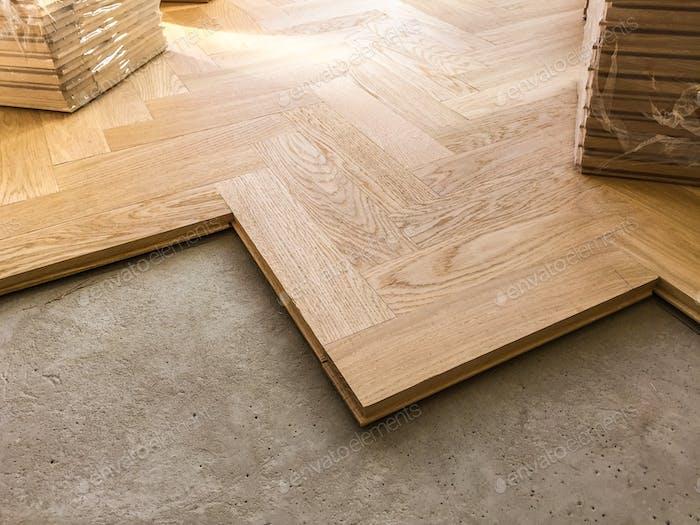 Wood parquet flooring being laid on a kitchen floor