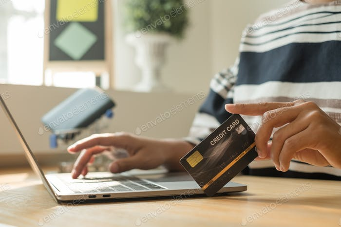 The businesswoman's hand is holding a credit card and using a laptop for online shopping and interne