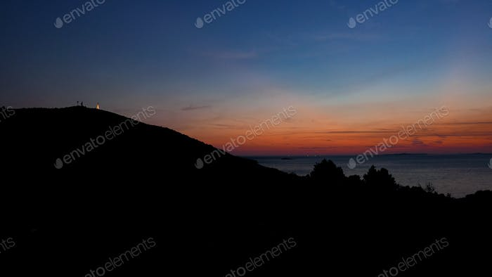 Sunset at the sea. Silhouette of a hill with a small beacon on top of it.