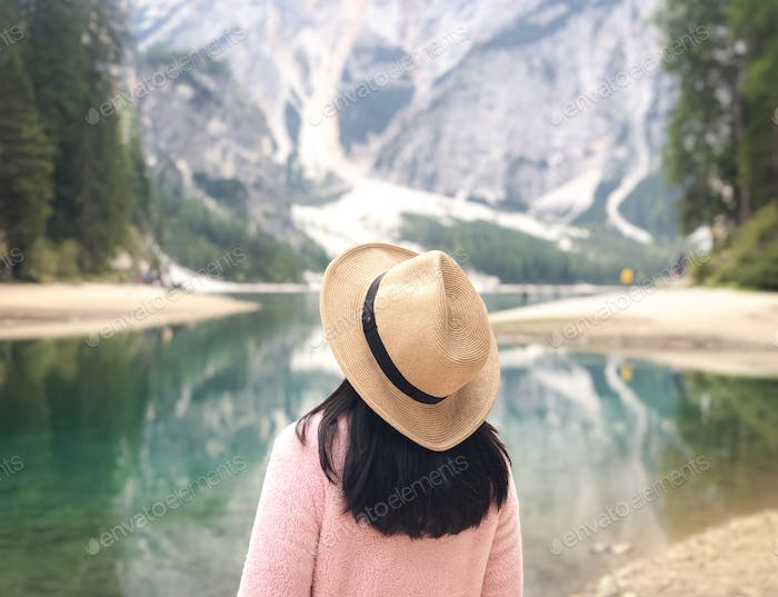 People from behind wearing hat stands in front of beautiful nature of lake and mountain in Dolomites