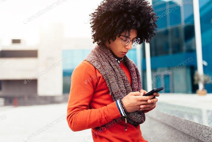 Mixed race man using smartphone outdoor