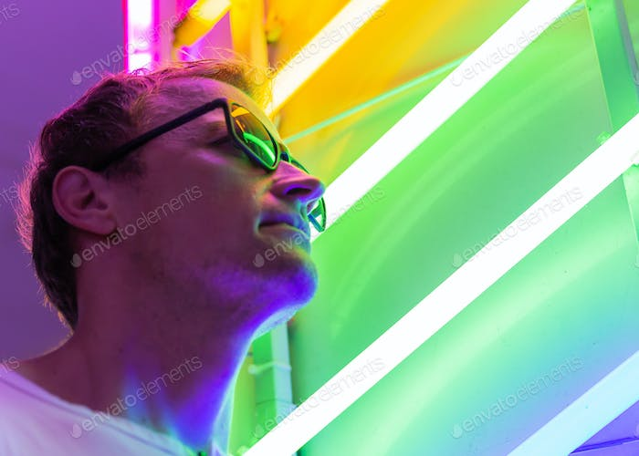 Man wearing shades looking up in front of neon lights