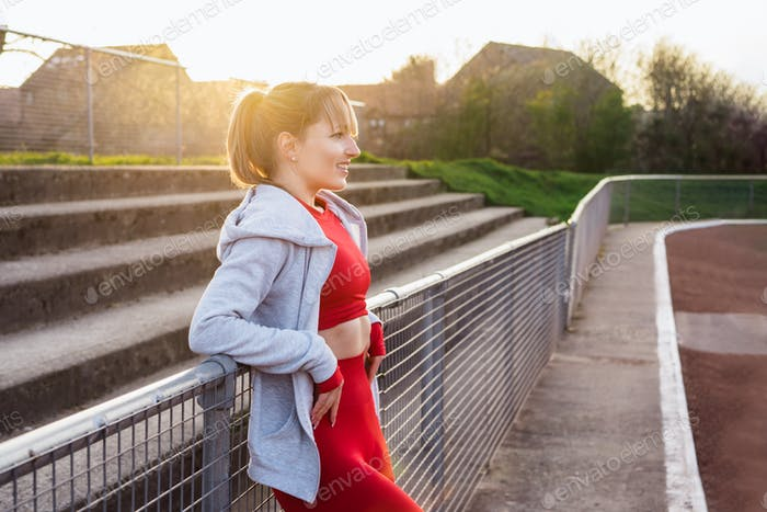 Portrait of a smiling confident fitness woman in red sport wear resting after work out outdoors
