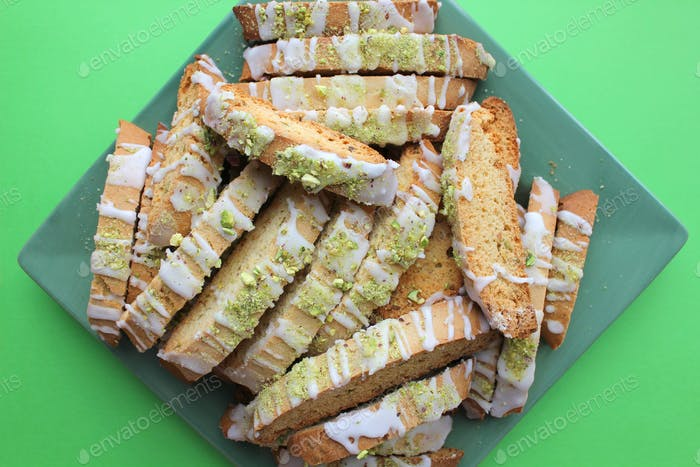 Pistachio and lime biscotti on a green background