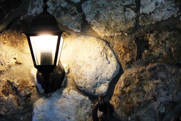Streetlight in a summer arbor on a wall from a stone