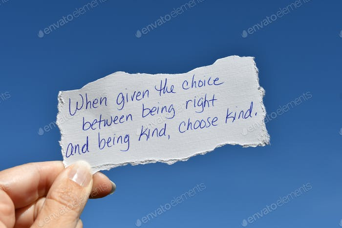 Female holding handwritten note When given the choice between being right & being kind, choose kind