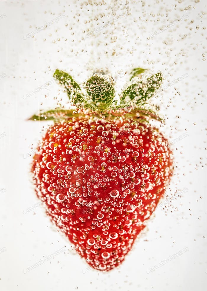 Red strawberry submerged in water with bubbles