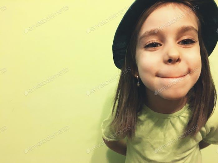 Little girl against green wall