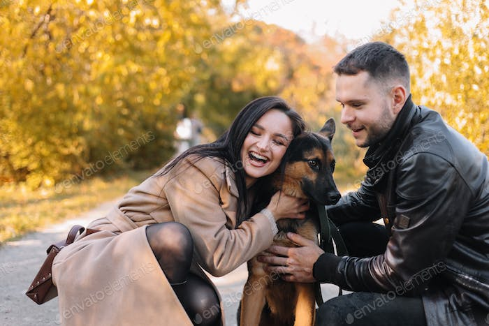 Happy loving couple walking with dog in autumn park outdoors outdoors