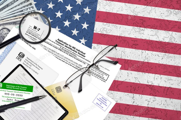 IRS form W-7 Application for IRS individual taxpayer identification number lies on flat lay office