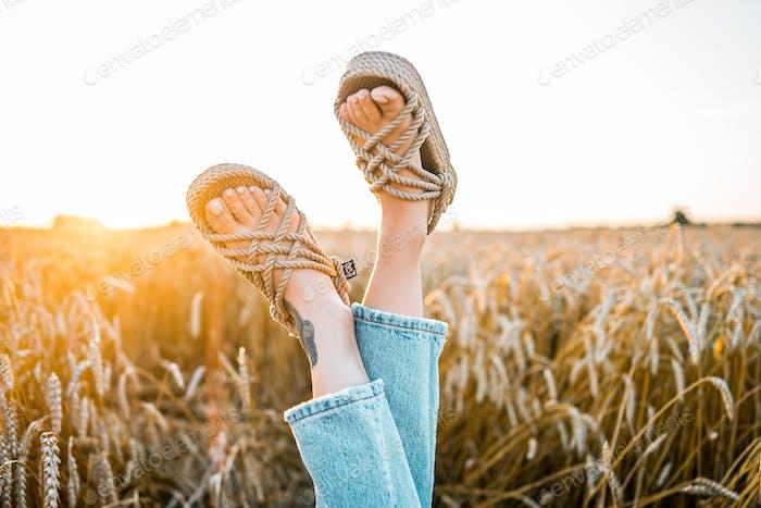 Legs in rope sandals in wheat field
