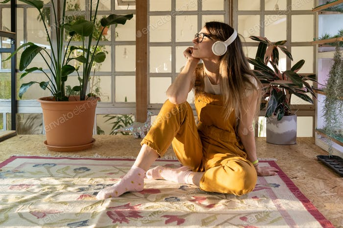 Satisfied casual woman wear earphones listen to music relaxed after day of work from home office