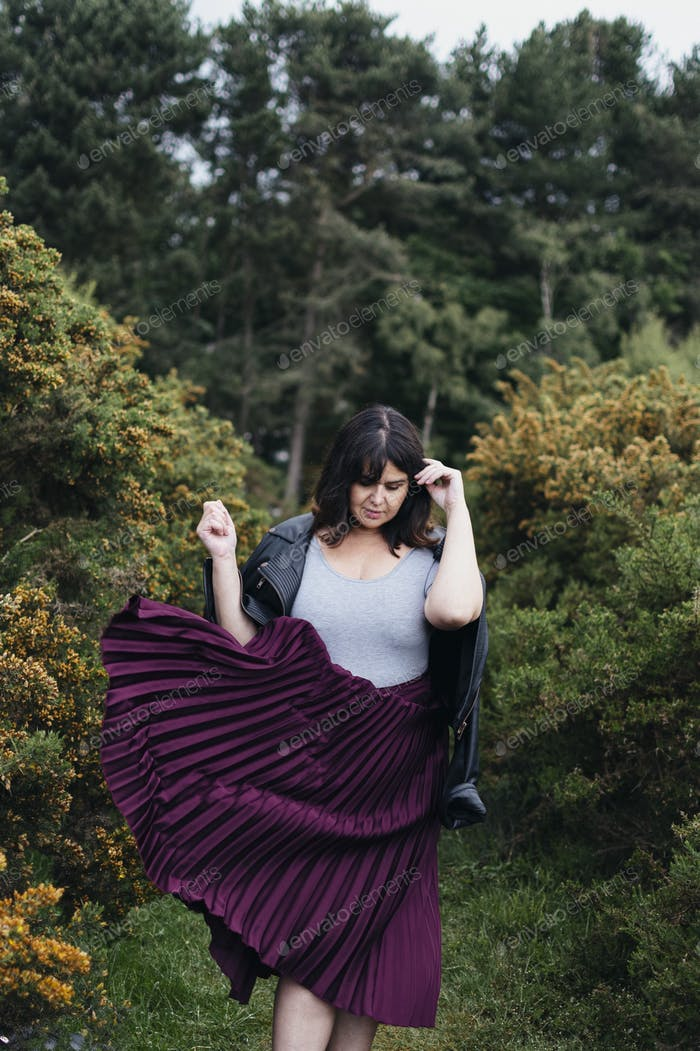 Stylish woman in park setting wearing pleated skirt