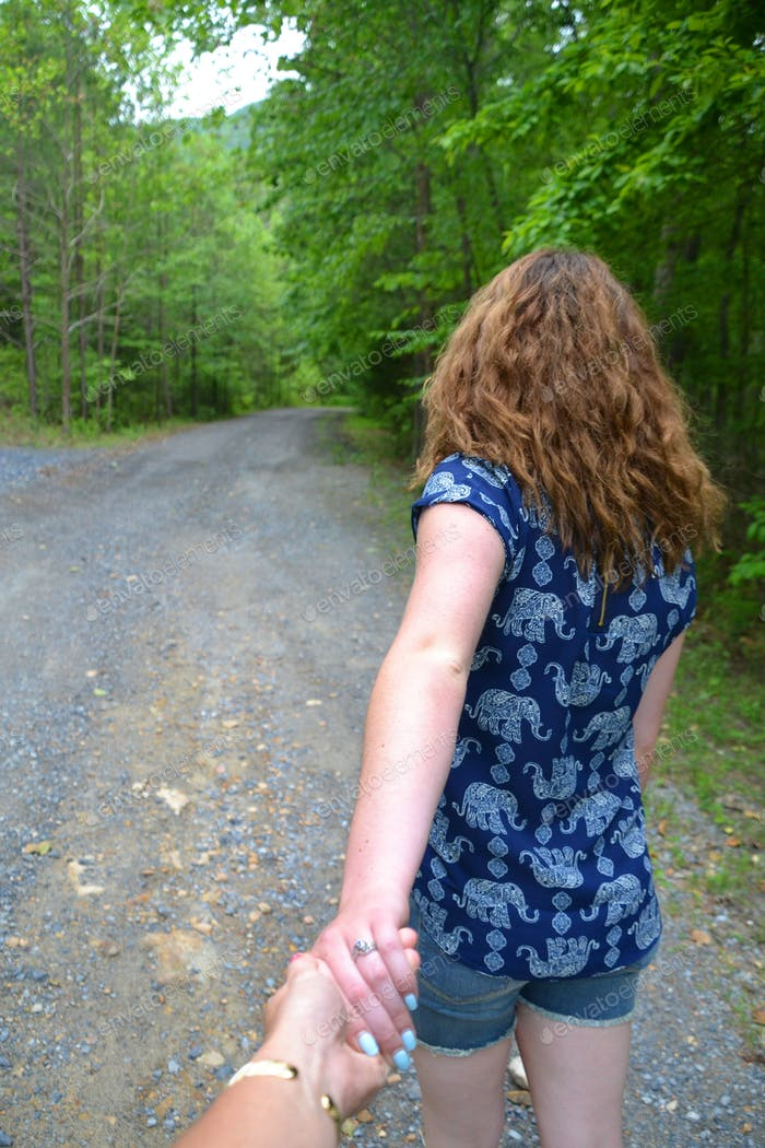 A female (young woman) leading the way down a gravel lane in the woods - follow me - holding hands -