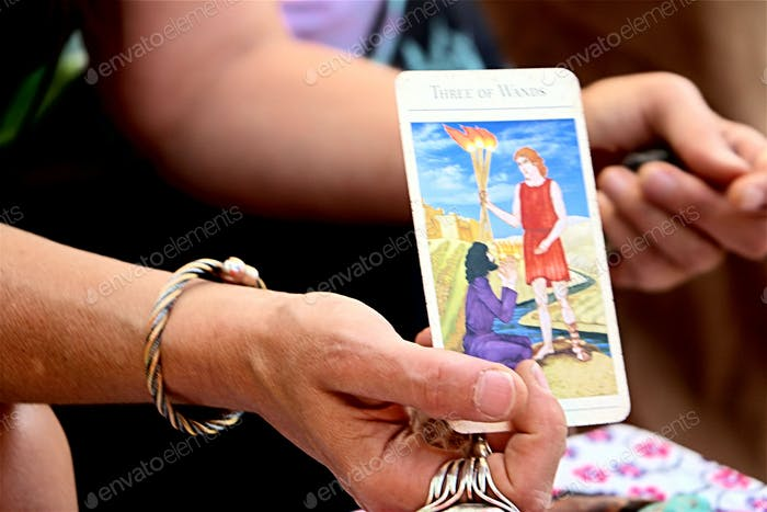 Mystic:  Tarot card reader shows card pulled from deck to person having reading.
