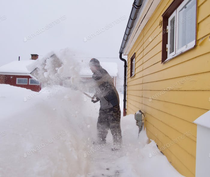 snowfall in the North of Sweden, man removing snow with a spade