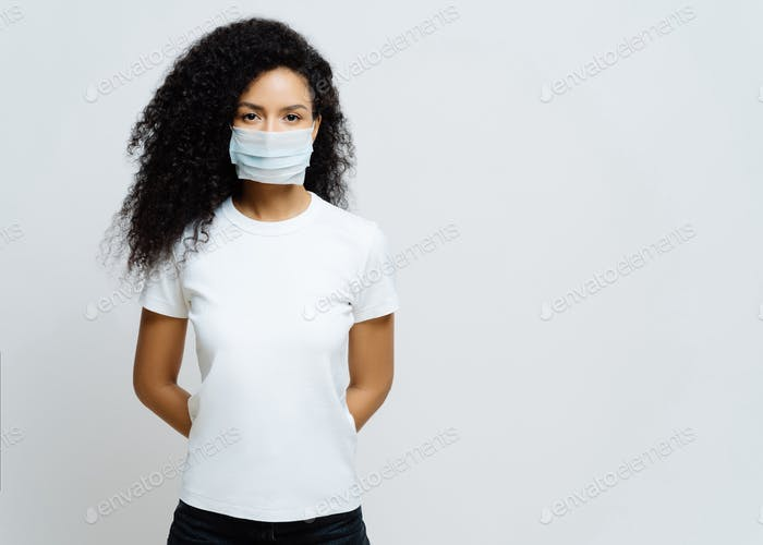 Afro American woman being on self isolation or quarantine, wears medical mask during coronavirus