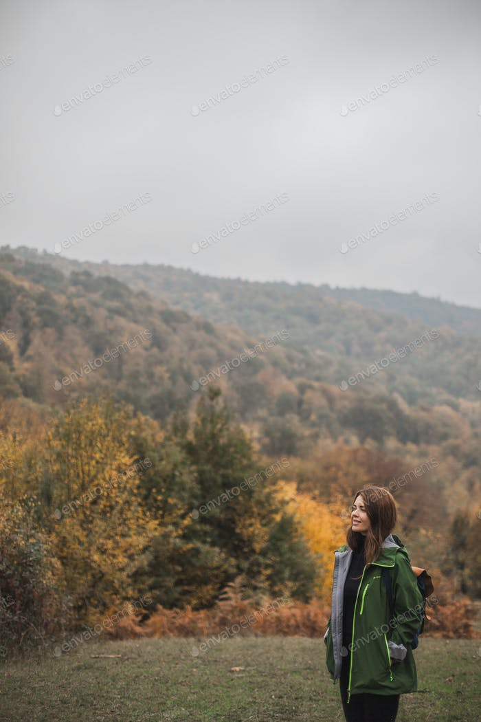 a girl stands in the forest enjoying the beauty of autumn after the rain