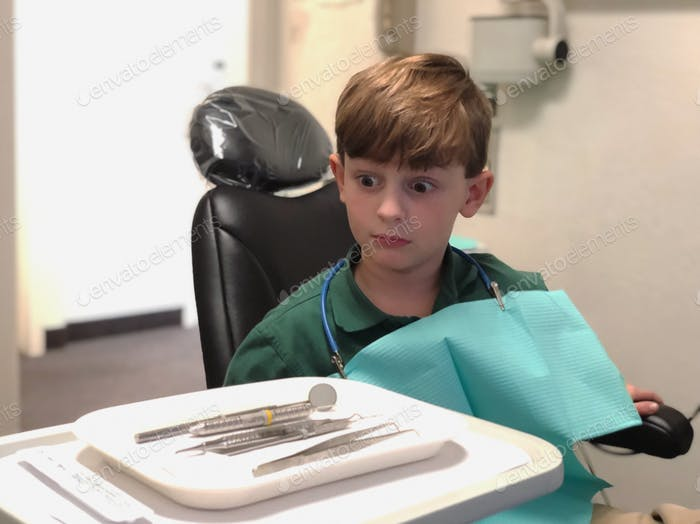 Kleiner Junge beim Zahnarzt. Zahnreinigung, ärztliche Verabredung, weite Augen, lustiges Gesicht, Kindheit, er