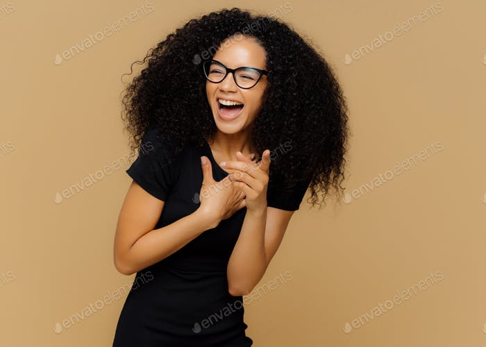 Overjoyed female laughs out loudly, notices funny scene, points at camera, wears transparent glasses
