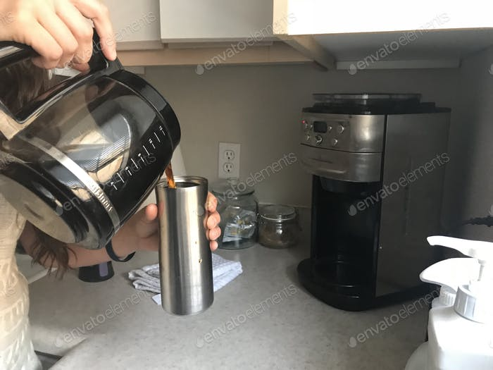Morning routine of pouring coffee into an insulated coffee cup