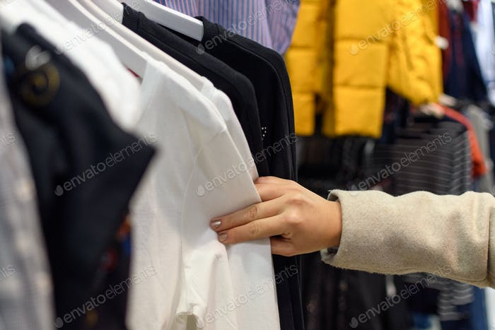 Selective focus of woman shopping in retail store, clothes, clothes, unrecognizable person.