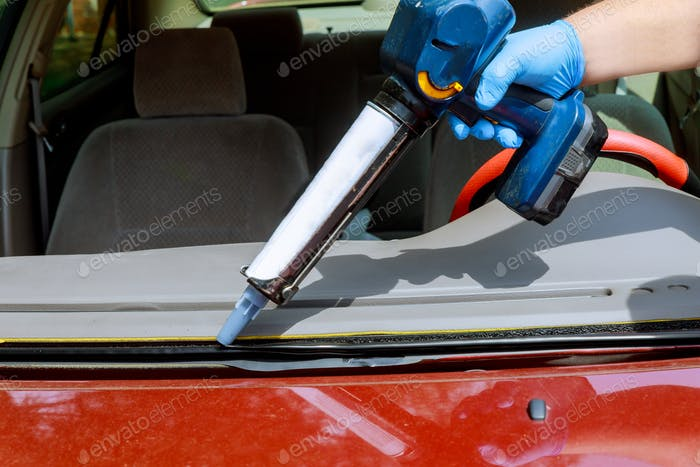 Close up car glaze worker silicone glue a windshield of a car at a service station glass for