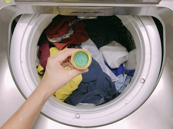 A man holding a cup of detergent on laundry day