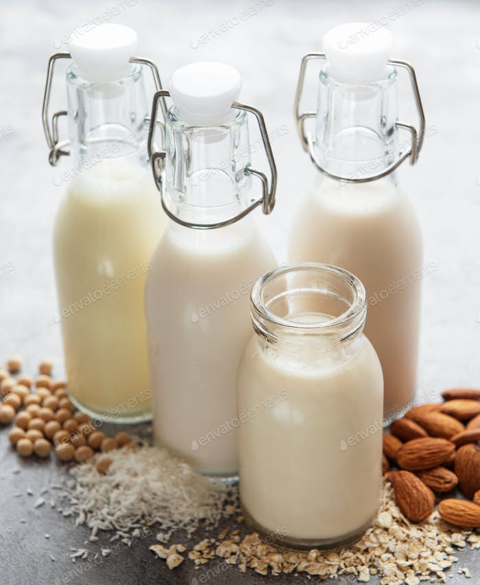 Bottles with different plant milk - soy, almond and oat milk.