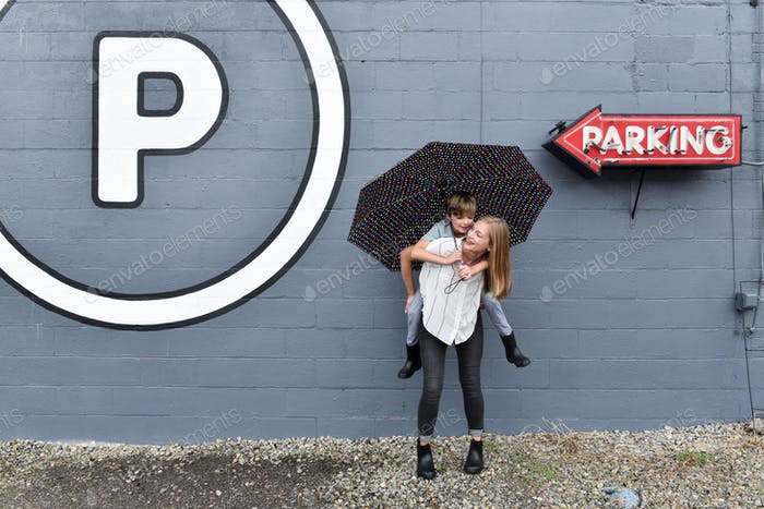 Smiling millennial woman giving a child a piggyback ride outdoors while holding an umbrella in the r