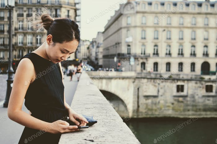 Beautiful woman awaiting messages on a bridge over the Seine river in Paris, France.