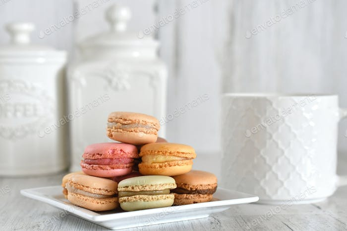 A plate of pastel French macaron cookies with a white coffee mug & canisters in bright airy kitchen