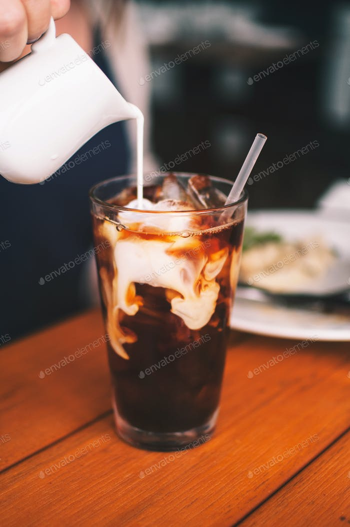 Person pouring milk/creamer into iced coffee at restaurant