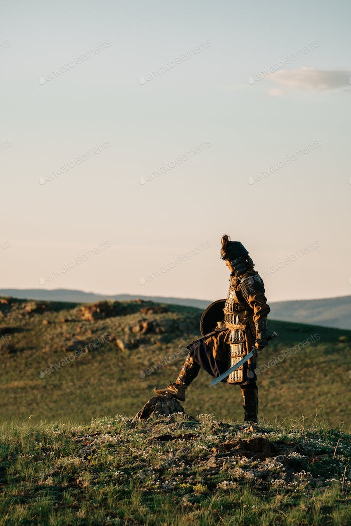 mongolian warrior standing on the ground in mongolian steppe in the sunset