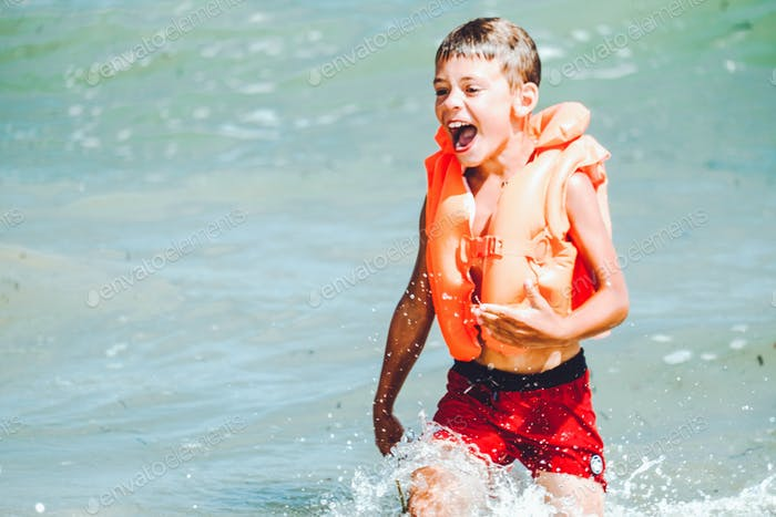 Happy laughing boy in orange inflatable vest swimming in the sea