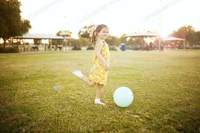 Mädchen treten einen Ball im Park