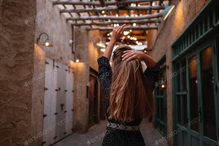 Happy woman traveler wearing black dress walking through the streets