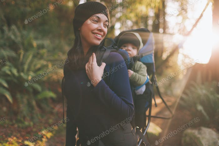 A mother hiking with a baby on her back.