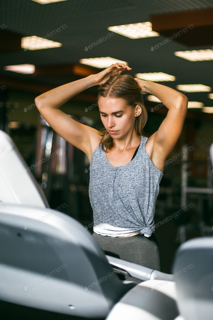 Attractive young sports woman is working out in gym. Doing cardio training on treadmill. Running on