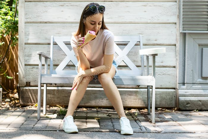 A young woman is sitting on a bench in the park and eating ice cream
