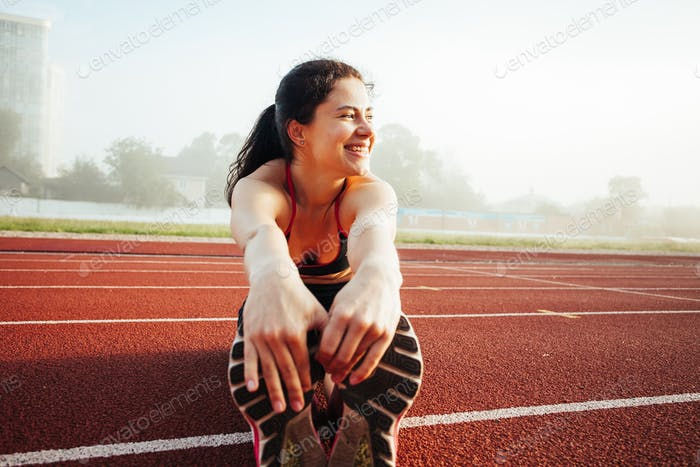 Athletic woman stretching on running track before training, healthy fitness lifesty