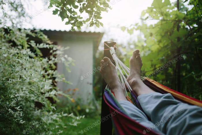 Male feet in hammock close-up, unrecognizable person, summer rest
