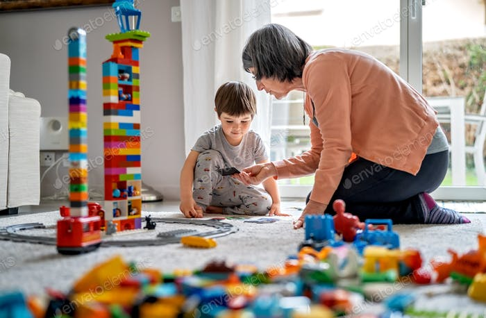 Little toddler boy playing with grandmother with Lego bricks at home at quarantine isolation period