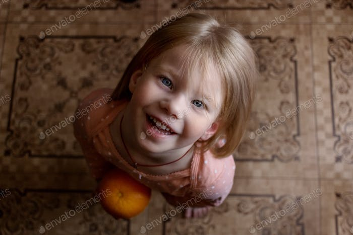 Little girl with orange. Emotions