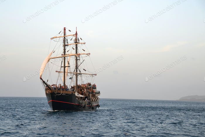 A tall masted pirate clipper ship sailing in the Caribbean sea ocean during golden hour