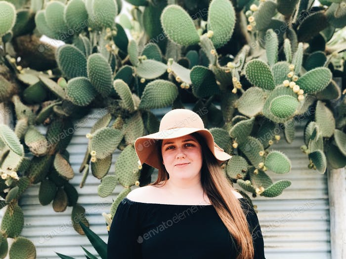 Smiling girl standing amongst cactus
