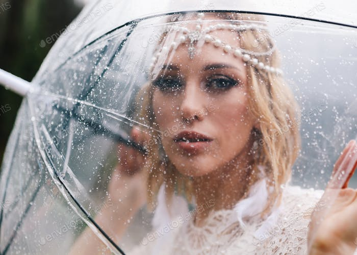 An attractive woman bride in a fashionable wedding dress with an umbrella stands in the rain on sea