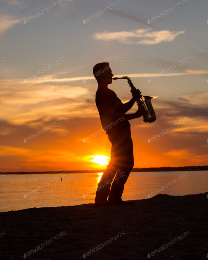 Silhouette saxophone player at sunset on the beach