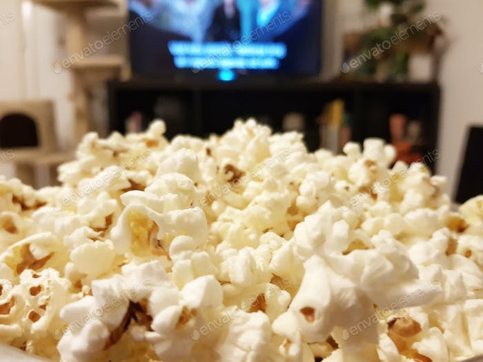 Close-up selective focus image of popcorn in front of tv.
